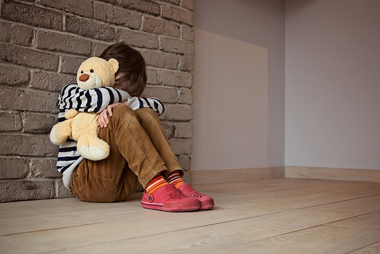 Child in corner with teddy bear